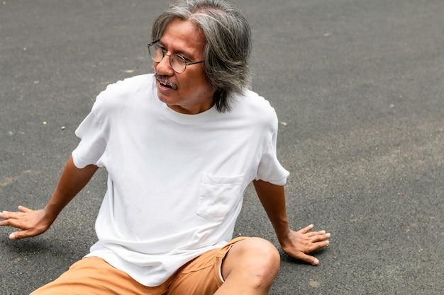 年配の男性人のアジアのストレスと公園でジョギングした後疲れています。
