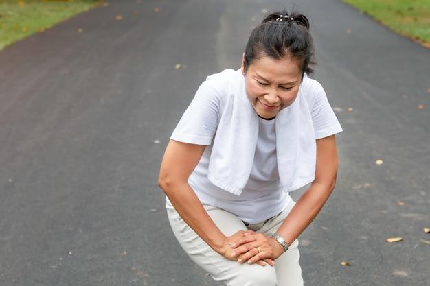 年配の女性のアジアの足の公園で実行中の痛み。