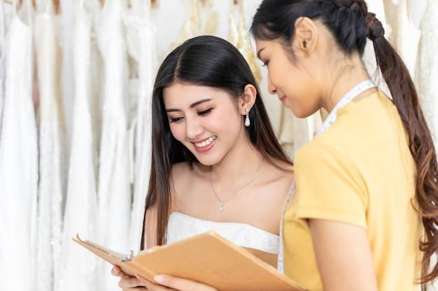 Красивая азиатская дама выбирая платье в магазине с ассистентом портноя.