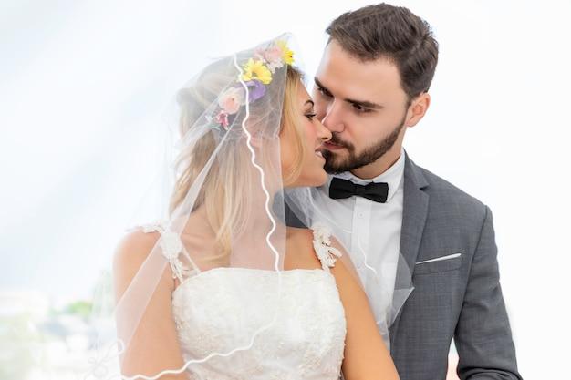 白人の新郎新婦カップルはキスし、結婚式のスタジオで抱擁します。