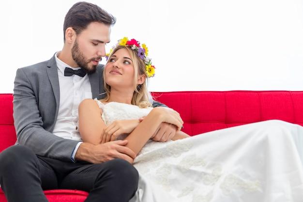 Пары жениха и невеста кавказских целуют и обнимают на белой предпосылке.