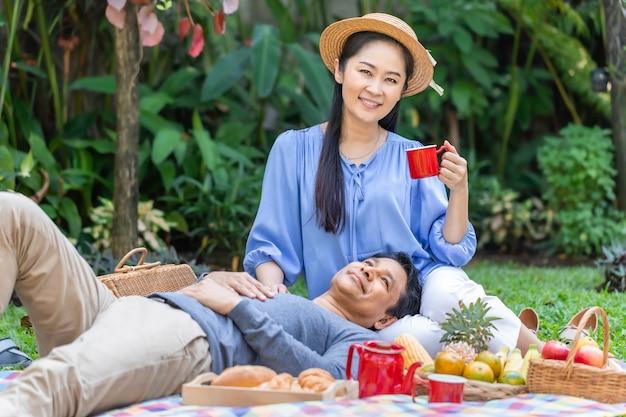 午前中に。公園でコーヒーとピクニックを飲むアジアのシニアカップル。