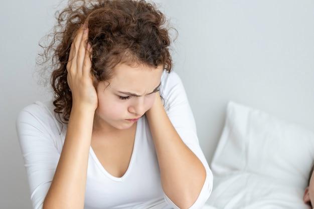 Кавказская пара в пижамах храпит и плохо спит в спальне. ее блокируют уши руками.
