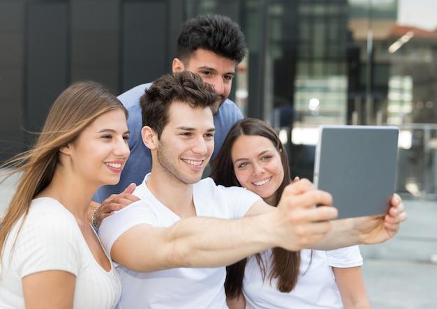セルフの写真を撮るためにタブレットを使用している友人のグループ