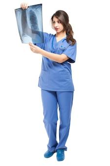 Женщина-врач, изучающая рентгенограмму легких
