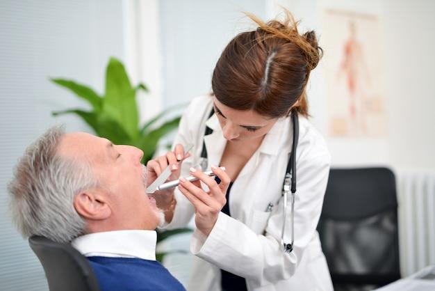 Врач, проверяющий горло пациента