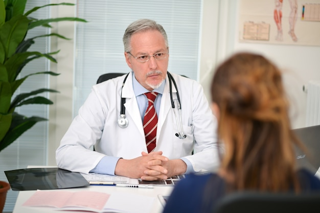 訪問中に患者を聴く医者