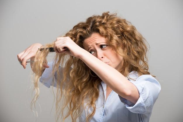 彼女自身の髪をカットする女性