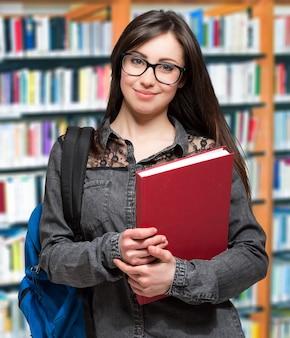 ライブラリーの美しい笑顔の学生