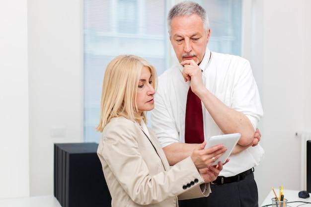 Бизнес-коллеги, используя планшет в своем офисе