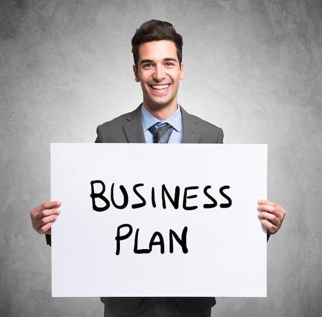 ビジネスプラン、言葉でパネルを持っている笑顔の若いビジネスマンの肖像