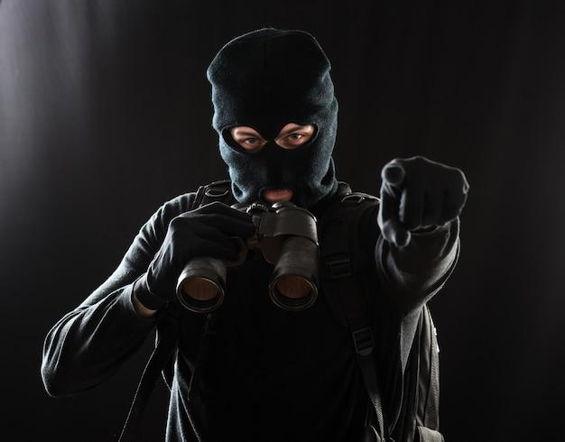 Вор в черной одежде с биноклем и указывая пальцем на цель