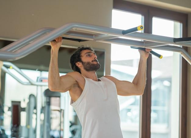 ジムで自由な体操のプルアップをやっている男