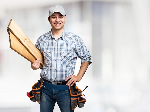 Портрет улыбается плотник держит деревянные доски. яркий фон