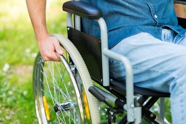 Парализованный человек с помощью инвалидной коляски