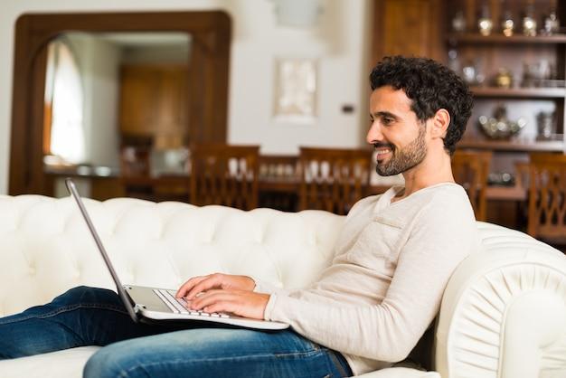 ソファー、座っている、ラップトップを使用している男