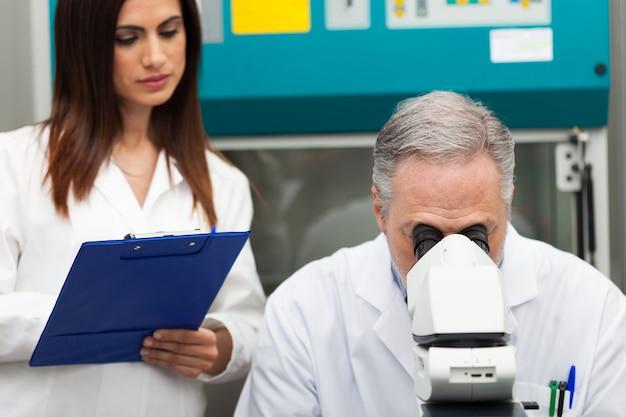 Старший ученый, использующий микроскоп в своей лаборатории