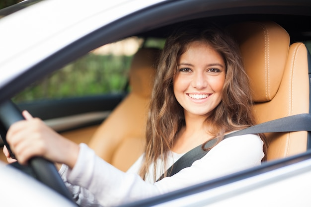 彼女の車を運転している若い女性