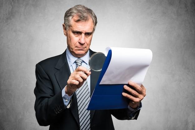 Бизнесмен с помощью увеличительной линзы для анализа контракта