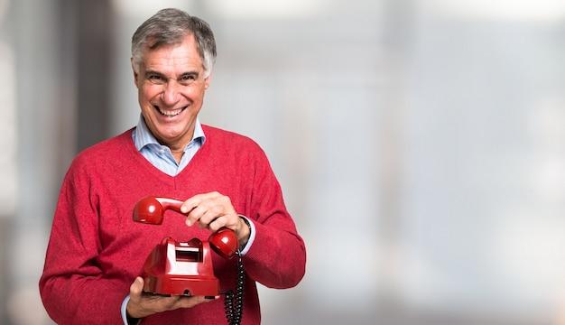 Человек, используя красный старинный телефон