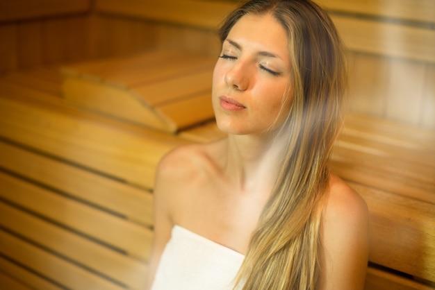 美しい女性がスチームルームにサウナ風呂を持つ