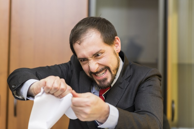 Злобный бизнесмен, разрывающий документ в своем кабинете