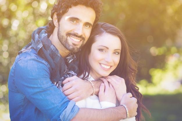 屋外で恋に魅力的な若いカップルの肖像画を閉じます