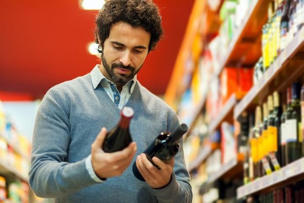 ワインを選ぶスーパーマーケットの男性