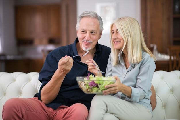 彼らのアパートで混ぜたサラダを食べるカップル