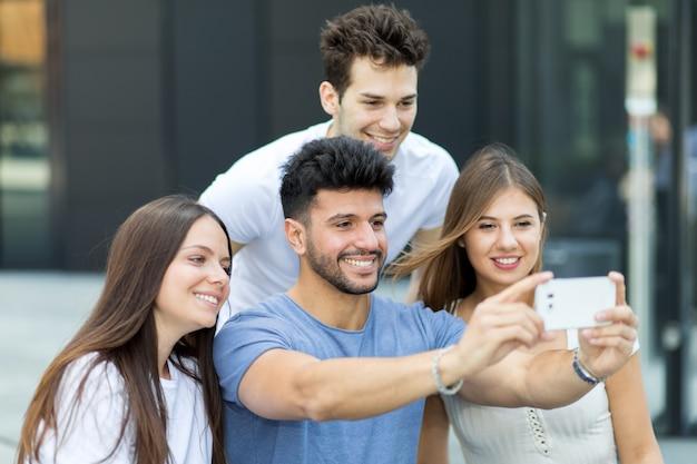 セルフの写真を一緒に撮っている友人のグループ