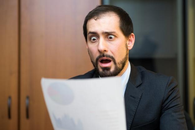 Удивленный человек, глядя на бизнес-документ в своем офисе