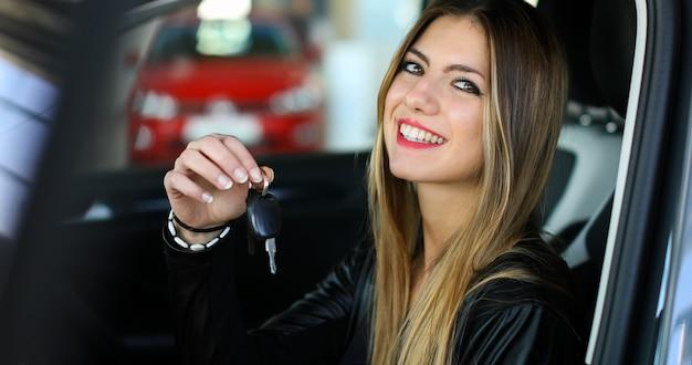 若い女性が彼女の新しい車の鍵を見せて