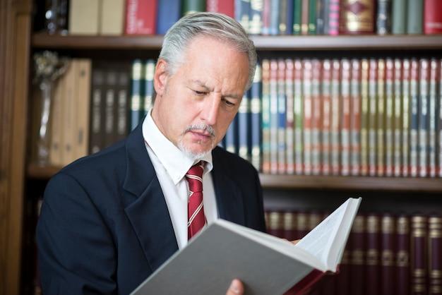 彼の図書館で本を読むビジネスマン