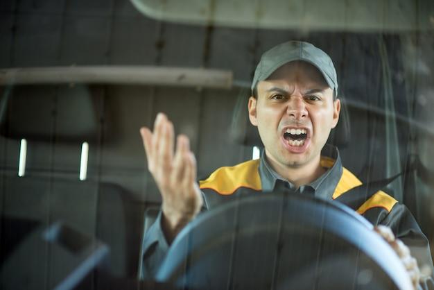 彼の車の中で叫んでいる怒っているドライバー