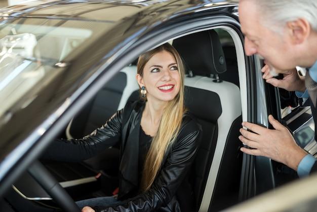 ショールームで彼女の新しい車を買うためにセールスマンに話している女性