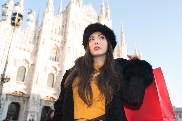 クリスマス前にミラノでのショッピングの若い女性の笑みを浮かべてください。