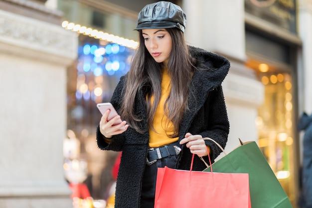 スマートフォンを使用しながらミラノでのショッピングミラノの美しい若い観光客の女の子