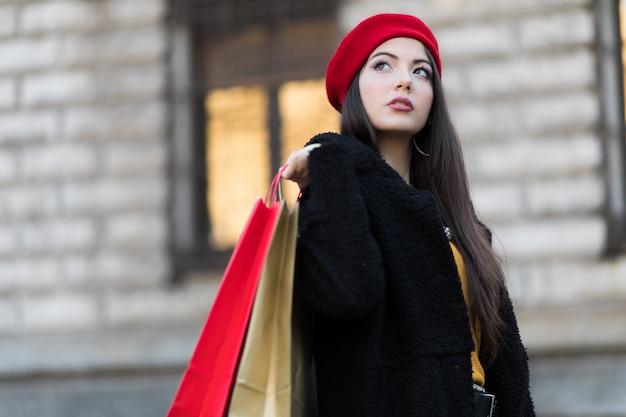 買い物袋とミラノ、イタリアのクリスマスプレゼントを持つ若い女