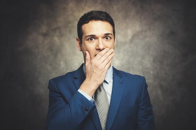 面白い実業家は彼の手で口を覆っています。
