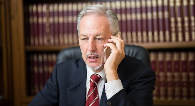 Старый деловой человек разговаривает по телефону