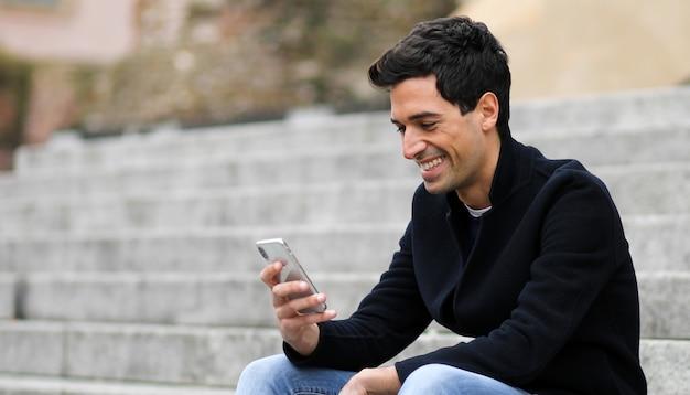 屋外の階段に座っているスマートフォンを使用して若い男
