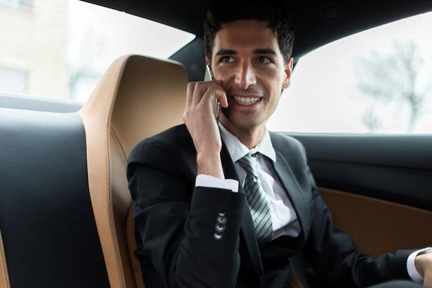 Менеджер по телефону сидит на заднем сиденье автомобиля