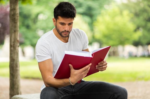 ハンサムな若い男が公園のベンチで本を読んで