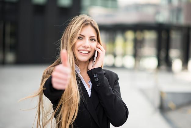 電話で話して笑顔のビジネス女性と親指