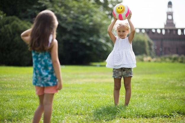 Две маленькие девочки играют с мячом