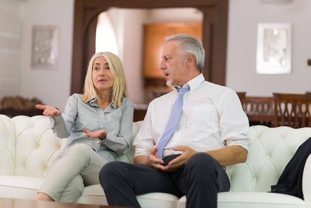 Счастливая зрелая пара разговаривает в своем доме