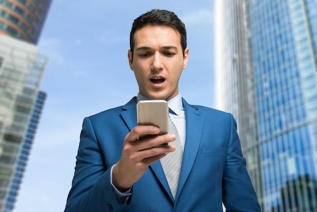 Удивленный бизнесмен, глядя на свой мобильный телефон