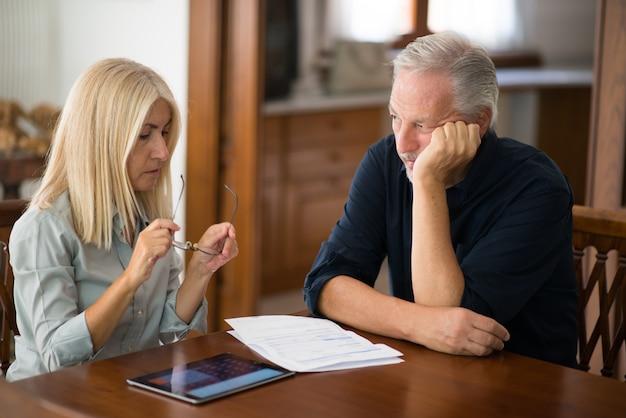 年配のカップルが一緒に生活費を計算します。