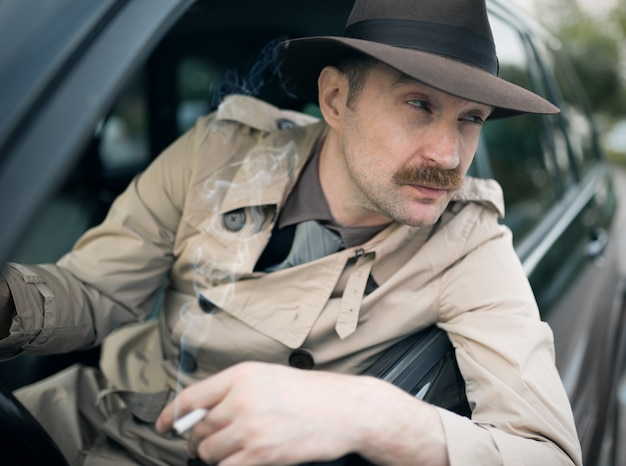 彼の車の中で誰かを待っている探偵