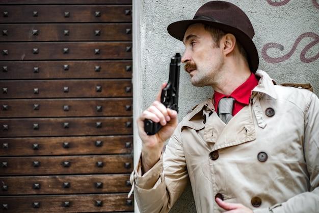 探偵はカバーを取り、彼の拳銃を目指して